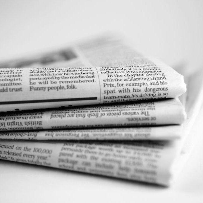 A close up black and white image of a stack four broadsheet newspapers with English text, casually piled up on a plain white background. The macro image is shot with a shallow depth of field, with only generic text visible. With copyspace.