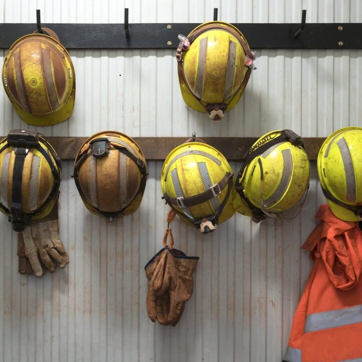 Safety helmets and gloves hang from a rack on a mining site